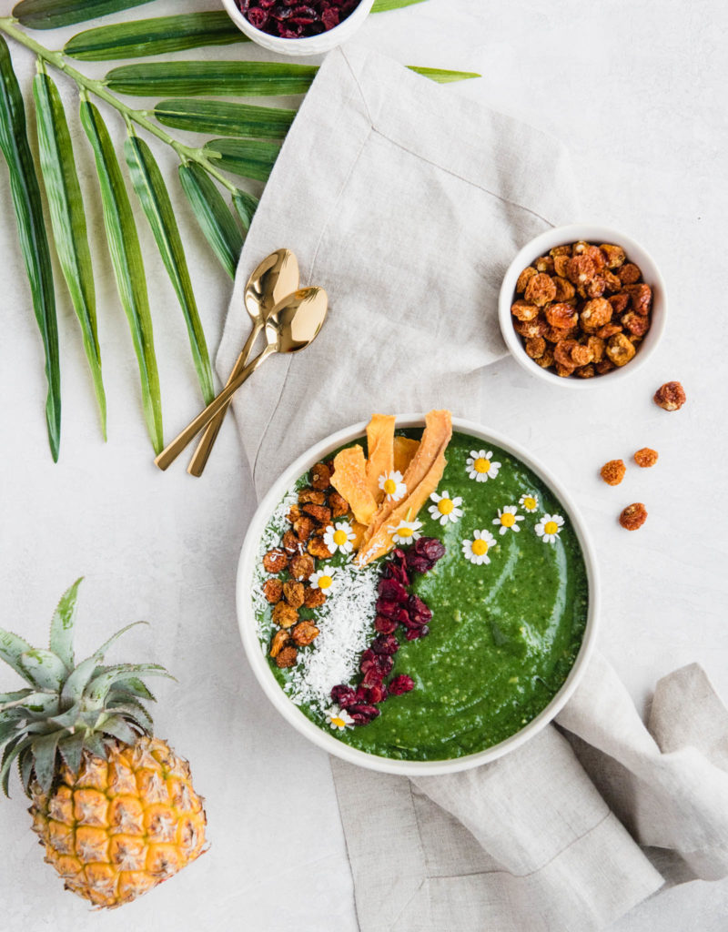 tropical smoothie bowl made with greens and tropical fruit, topped with dried fruits and coconut